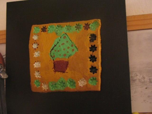 Na leseni deski nalepljena slika iz DAS mase (narejeno v šoli)